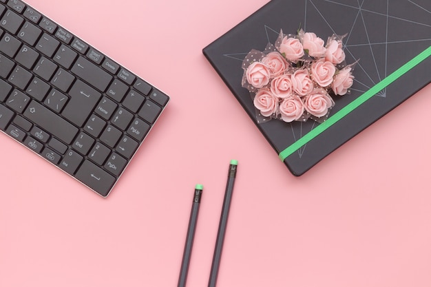Vista superior, caderno com flores e lápis com o teclado no fundo cor-de-rosa.