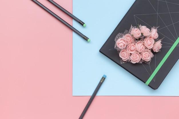 Vista superior, caderno com flores e lápis no fundo azul e cor-de-rosa.