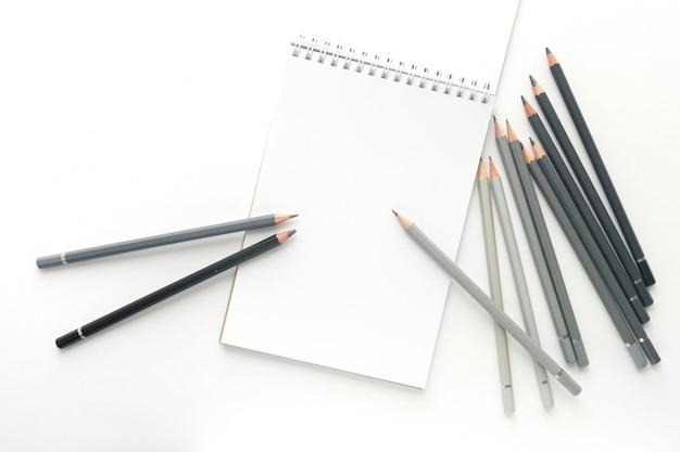 Vista superior, caderno com os lápis no branco.