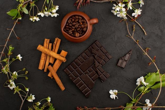 Vista superior café com canela e chocolate, com flores brancas no escuro
