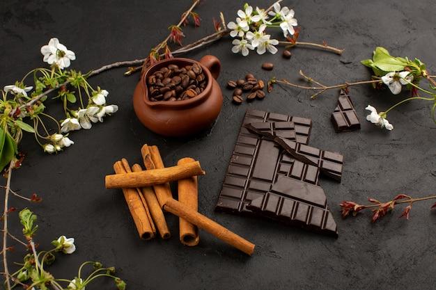 Vista superior, café com chocolate e canela, juntamente com flores brancas no chão escuro