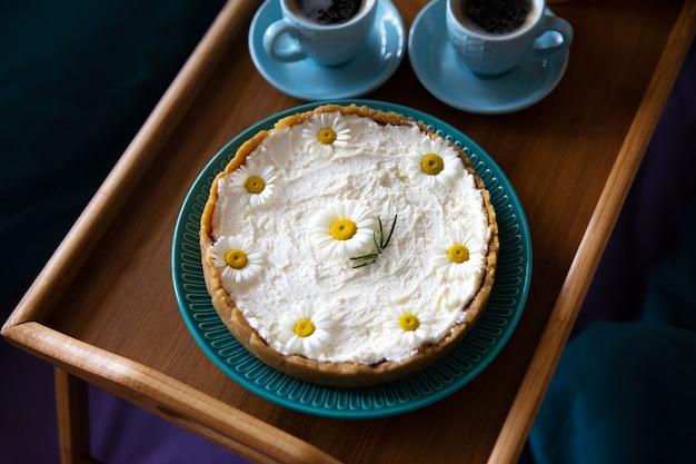 Vista superior - café da manhã na cama, um delicioso cheesecake e duas xícaras de café em uma bandeja de madeira.