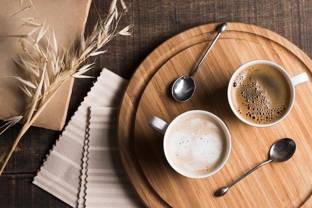 Vista superior café e café com leite em canecas brancas na placa de madeira