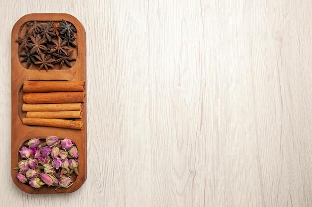 Vista superior canela fresca com flores na mesa branca flor planta de madeira
