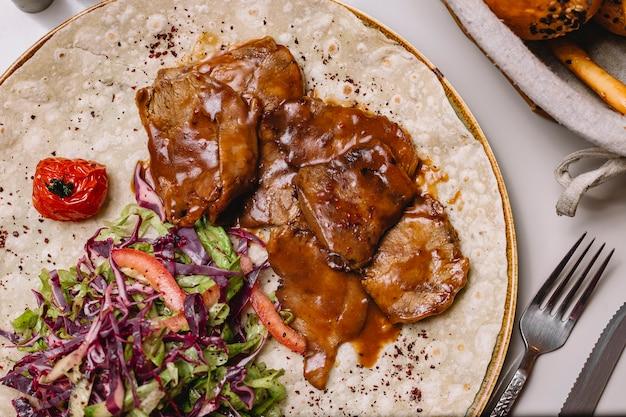Vista superior carne de vitela em molho no pão árabe com salada de legumes
