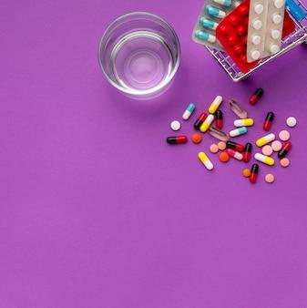 Vista superior carrinho de brinquedo com relógio e pílulas ao lado