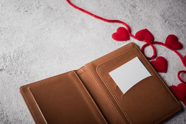 Vista superior cartão branco em branco na carteira e presente de coração