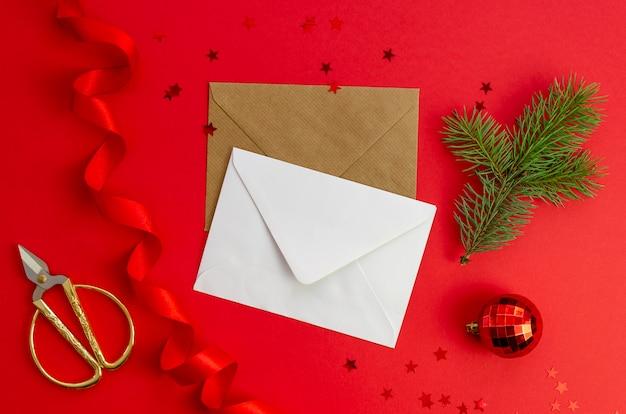 Vista superior cartão e envelope com decorações de natal, ramo de árvore de natal, bola de vidro e fita