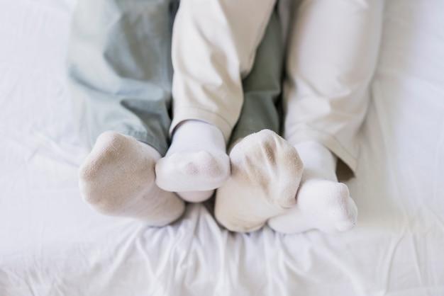 Vista superior casais pés juntos na cama