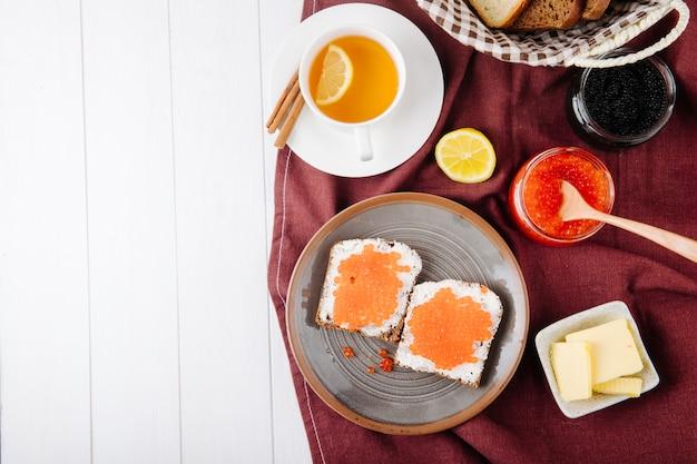 Vista superior caviar vermelho pão de centeio torrada com queijo cottage manteiga de caviar vermelho caviar preto pão branco xícara de chá canela fatia de limão e copie o espaço no fundo branco