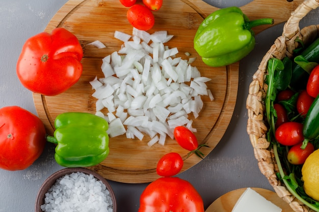 Vista superior cebola picada na tábua com tomate, sal, pimenta verde na superfície cinza