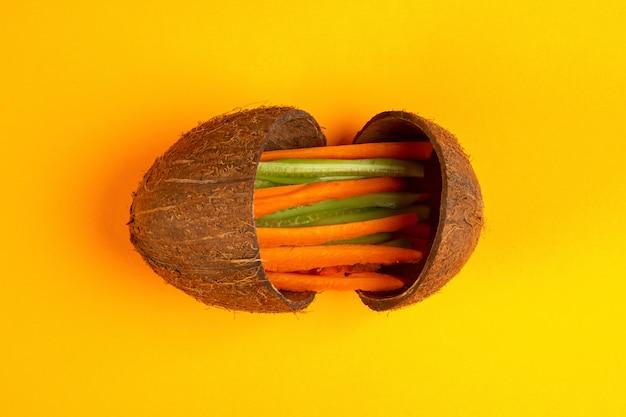 Vista superior cenoura picada com pepino em uma casca de coco em amarelo