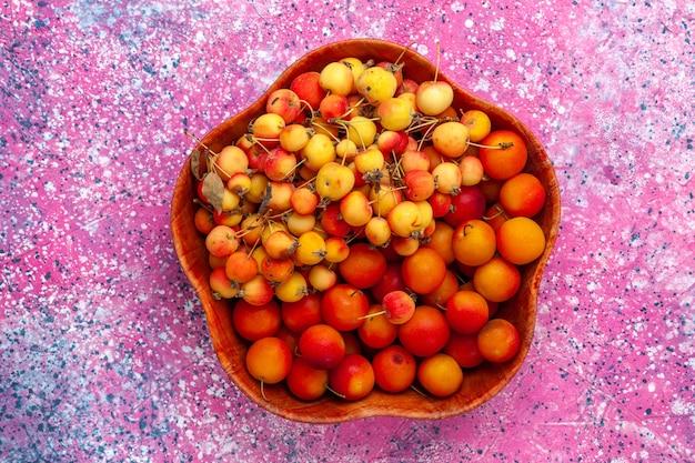Vista superior cerejas doces frescas com ameixas dentro do prato na mesa rosa.