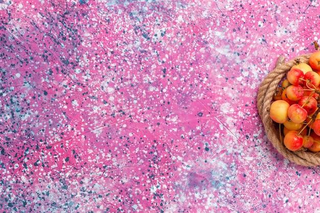 Vista superior cerejas doces frescas com cordas na mesa rosa.