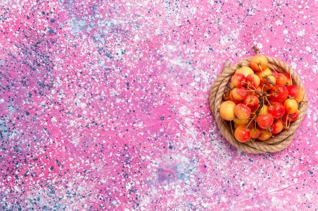 Vista superior cerejas doces frescas com cordas no fundo rosa.