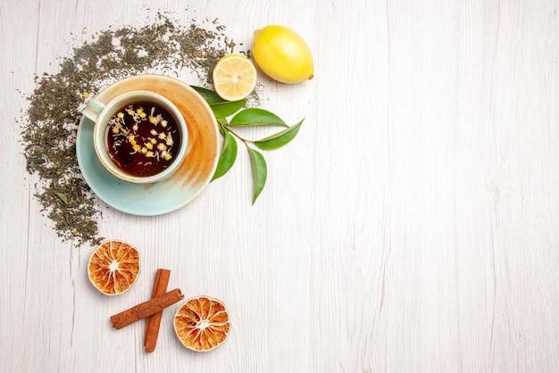 Vista superior chá de ervas xícara branca de chá de ervas ao lado das ervas limão e canela na mesa branca