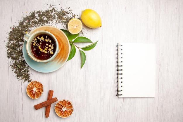 Vista superior chá de ervas xícara branca de chá de ervas ao lado do caderno branco ervas limão canela na mesa branca