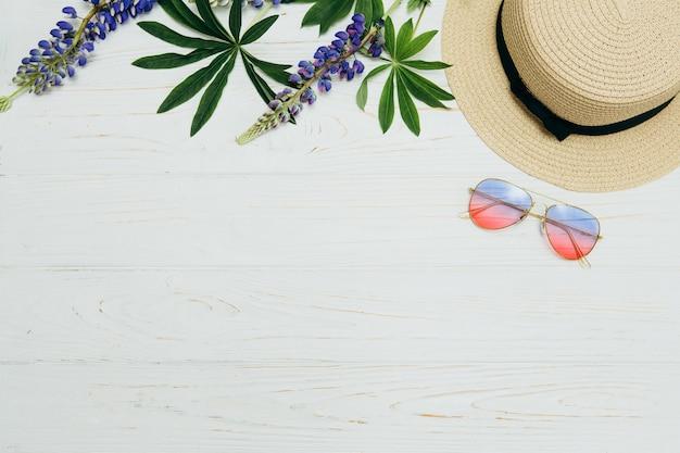 Vista superior, chapéu de palha, óculos escuros e flores sobre fundo branco