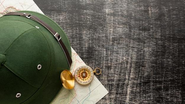 Vista superior chapéu e bússola sobre uma mesa