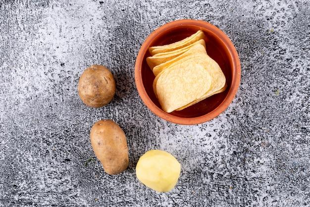 Vista superior chips em tigela com batatas frescas na pedra branca horizontal