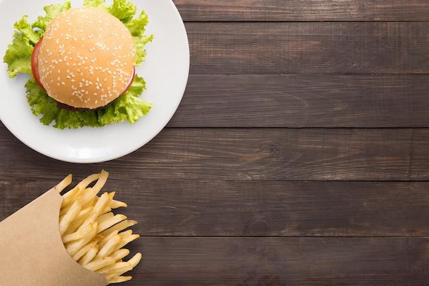 Vista superior churrasco hambúrguer e batatas fritas no fundo de madeira. copie o espaço para o seu texto