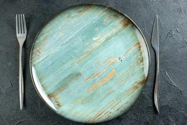 Vista superior ciano em placa redonda garfo e faca em superfície escura