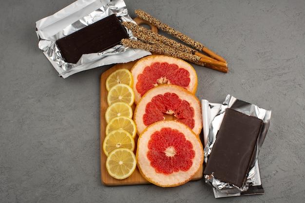 Vista superior, cítricos, fresco, azedo, maduro, suculento, limão, toranjas, juntamente com barras de chocolate e palitos de doces no chão cinza