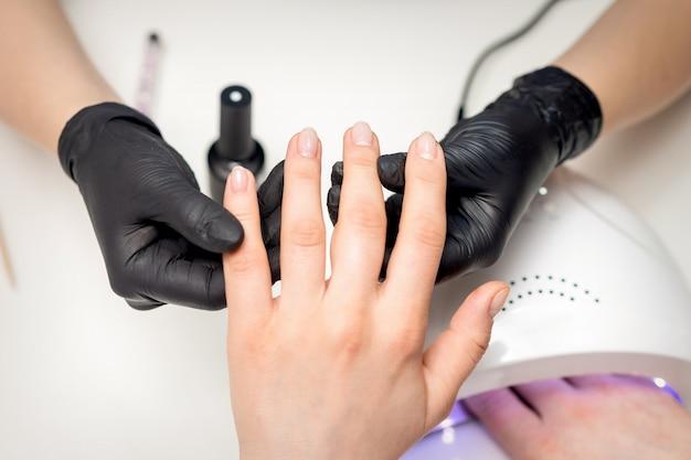 Vista superior close-up das mãos da manicure em luvas pretas estéreis segurando os dedos da cliente em salão de manicure