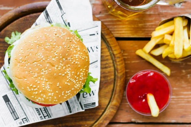 Vista superior close-up de hambúrguer e batatas fritas na placa de madeira