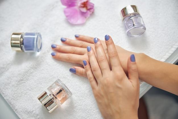 Vista superior close-up de mãos femininas com unhas de cor azul, deitado na mesa com frascos de esmaltes e orquídeas