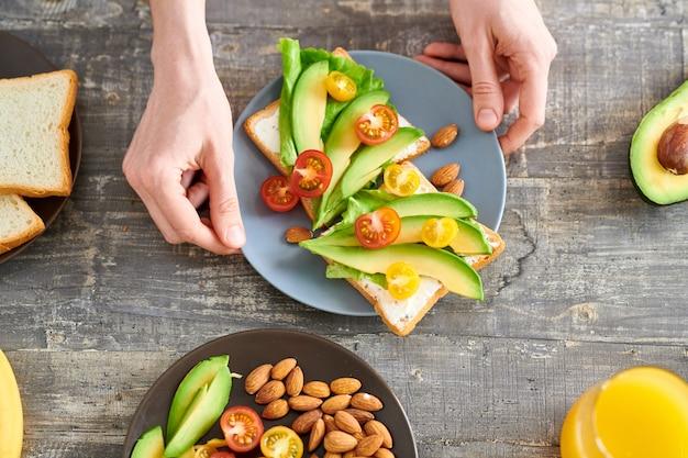 Vista superior closeup de jovem irreconhecível fazendo sanduíches com abacate no café da manhã saudável, cópia espaço
