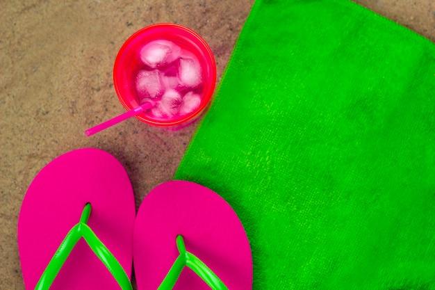 Vista superior coctail frio e chinelos em uma toalha verde em um bech