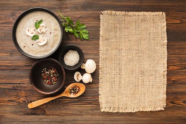 Vista superior cogumelos bisque condimentos e colher com material têxtil