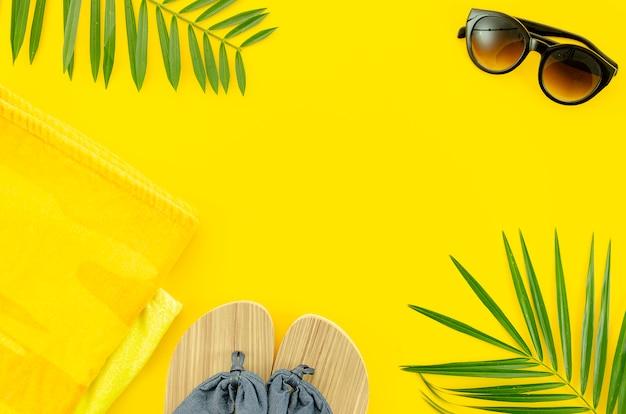 Vista superior coisas de verão para a praia, óculos escuros e chinelos.