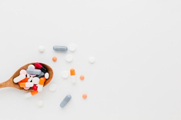 Vista superior, colher de pau cheio de comprimidos