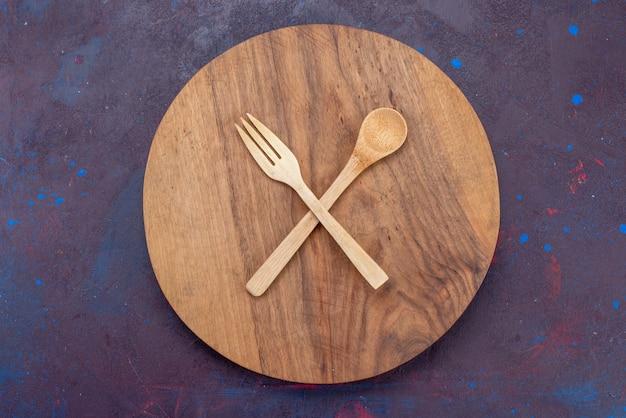 Vista superior colher garfo de madeira na superfície escura talheres de madeira