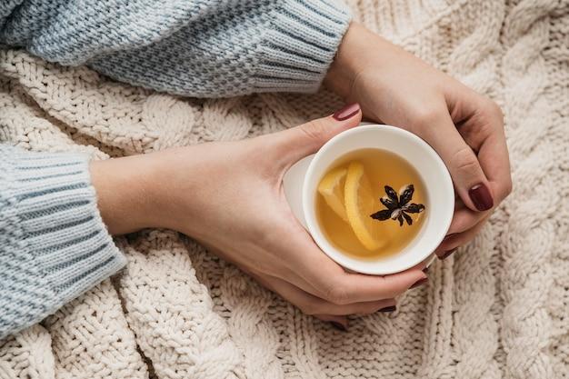 Vista superior com as mãos segurando uma xícara com chá e anis estrelado