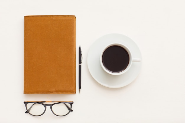 Vista superior com composição mínima de uma única xícara de café ao lado do planejador de negócios e óculos de aro preto