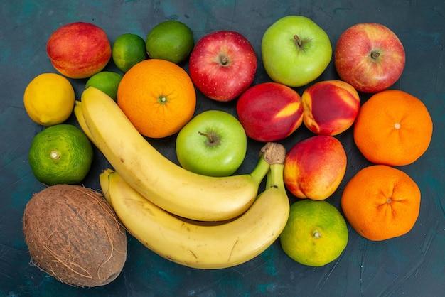 Vista superior com diferentes composições de frutas, bananas, tangerinas, maçãs, mesa azul escuro