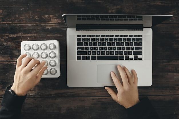 Vista superior com duas mãos trabalhando no laptop retina e no controle do mixer midi sem fio para fazer música