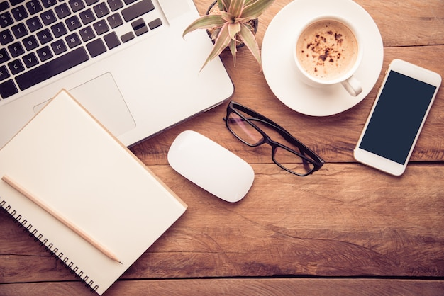 Vista superior com espaço de cópia, mesa de trabalho com laptop, celular, lápis de caderno e café