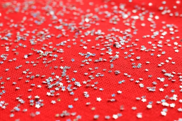 Vista superior com estrelas de natal prata. confetes de estrelas de prata sobre um fundo vermelho de malha. ano novo, plano de fundo de natal.
