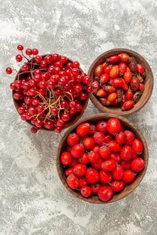 Vista superior com frutas vermelhas e frutas maduras em fundo branco claro