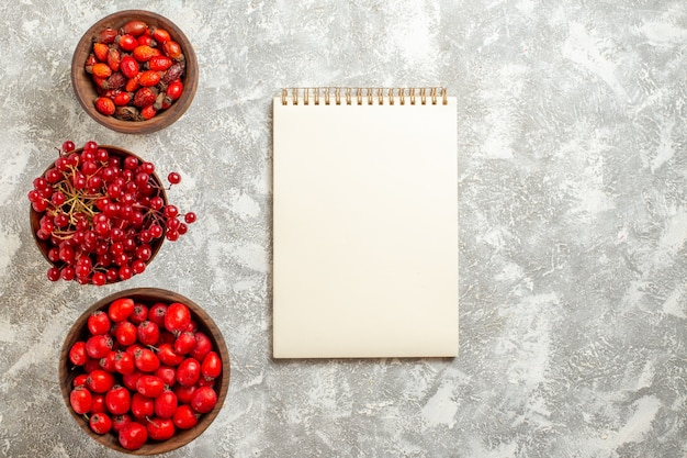Vista superior com frutas vermelhas e frutas maduras em fundo branco Foto gratuita