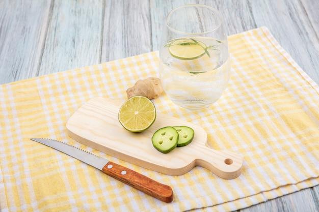 Vista superior com limão fresco na placa de madeira da cozinha com gengibre e faca na toalha de mesa xadrez amarela