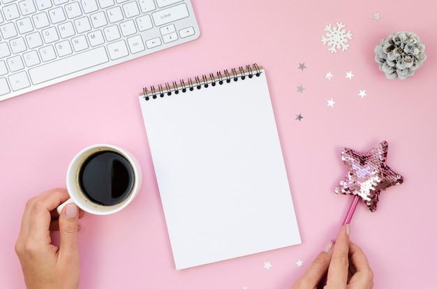 Vista superior com mãos femininas escrevendo em um caderno espiral vazio em uma mesa rosa com uma xícara de café