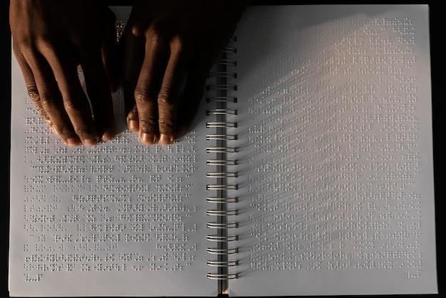 Vista superior com mãos lendo caderno braille
