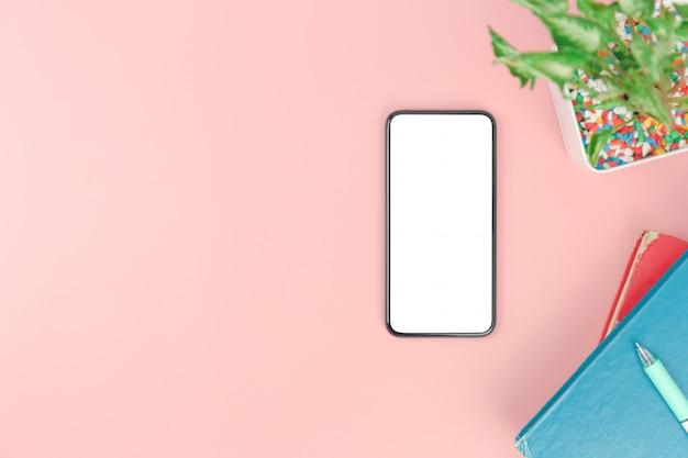 Vista superior com sobrecarga de caneta livros smartphone em fundo pastel rosa, plana leigos