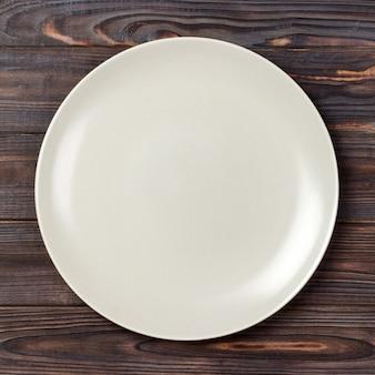 Vista superior com vazio para você projetar, prato branco vazio na madeira