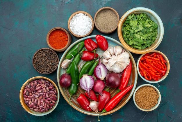 Vista superior compoisição de vegetais cebolas alhos verdes e pimentas na mesa escura refeição com vegetais, salada, foto colorida
